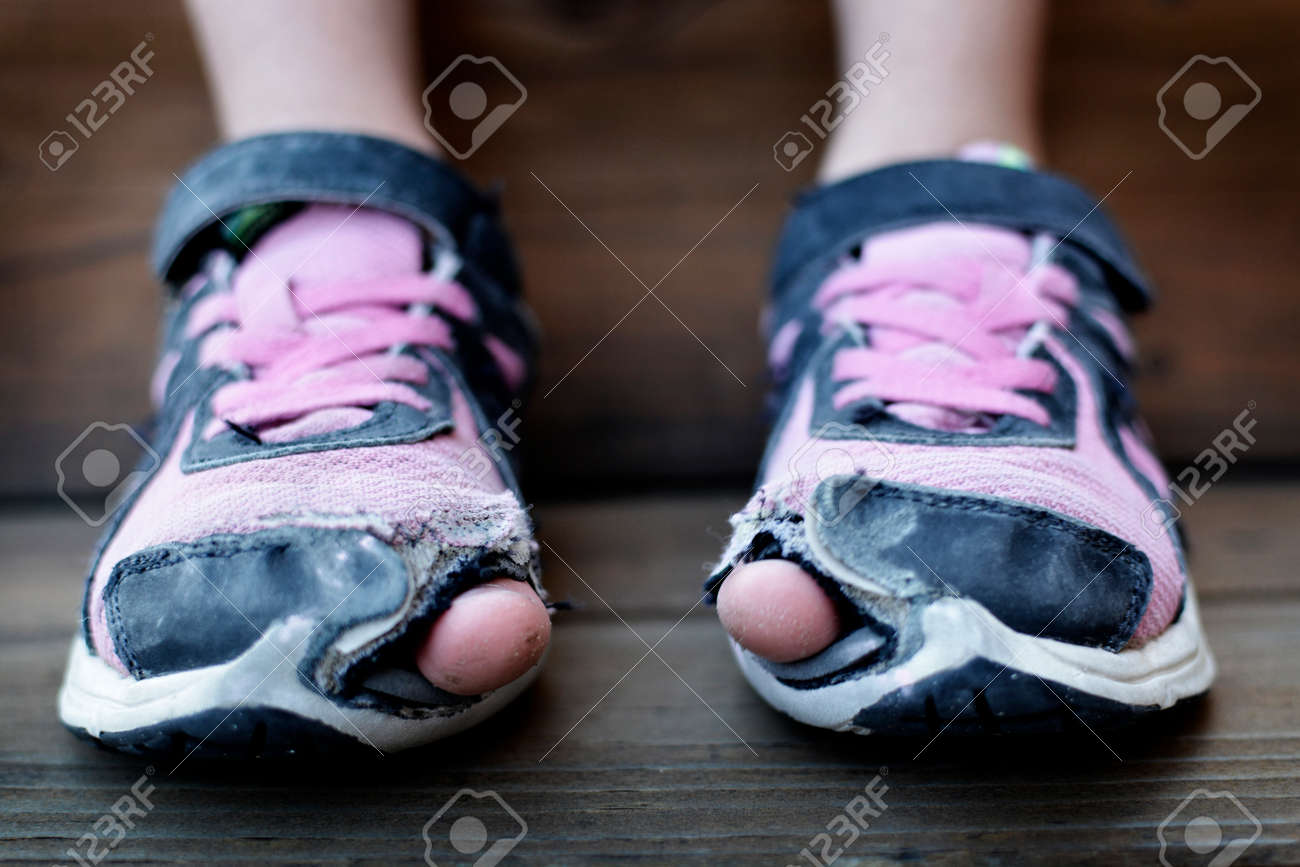 Homeless child wearing old worn out shoes on feet with holes in them toes sticking out - 155511970
