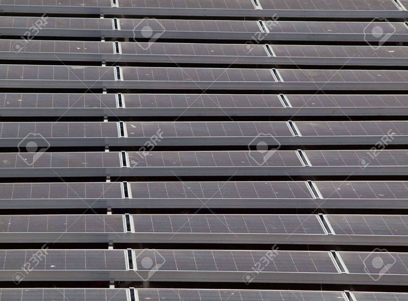 Flat-Roof top solar panel stretching into the distance on top of a baseball ballparks office.  Little bits of bird dropings can be seen on panels. Stock Photo - 7945955