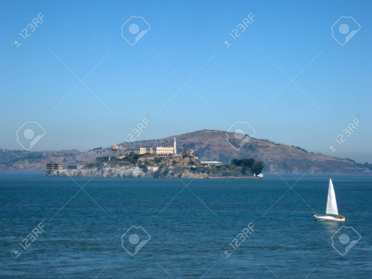 Alcatraz Island On A Nice Day With A Sail Boat In Front Of It