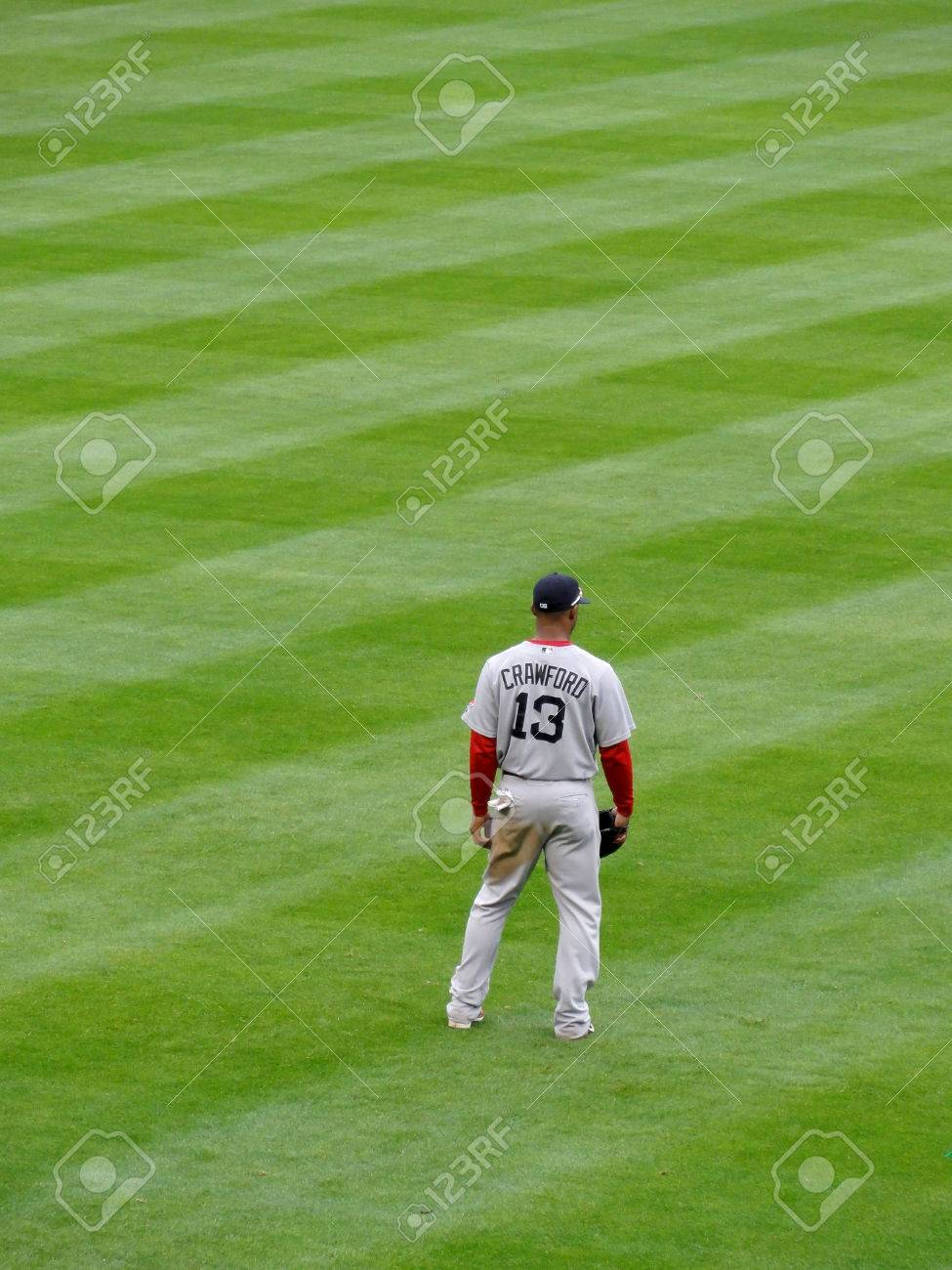 OAKLAND - APRIL 20: Red Sox Outfielder number 13 Carl Crawford stand in outfield with sunglasses on top of hat and dirt stain on pants in Oakland, California on April 20 2011. Stock Photo - 27929679