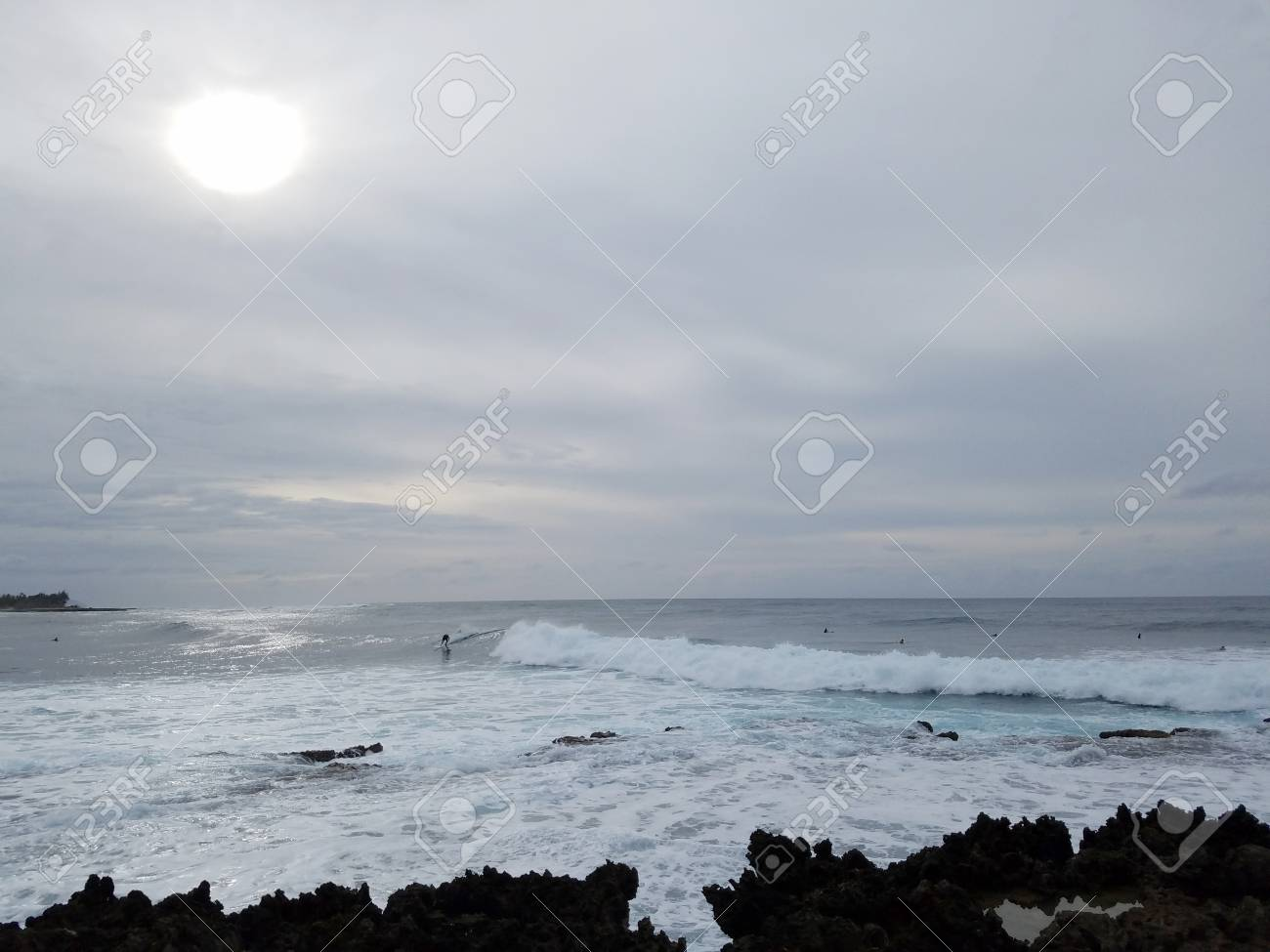 Waves Roll Into Shore With People Surfing With Clouds And Sun