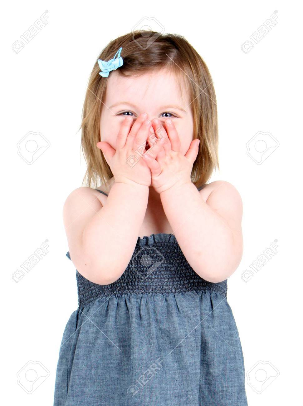 Cute little girl holding her hands over her mouth Stock Photo - 7459130