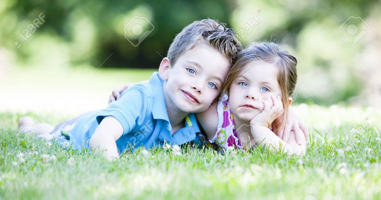 Two children laying in the grass while embracing Stock Photo - 10338816