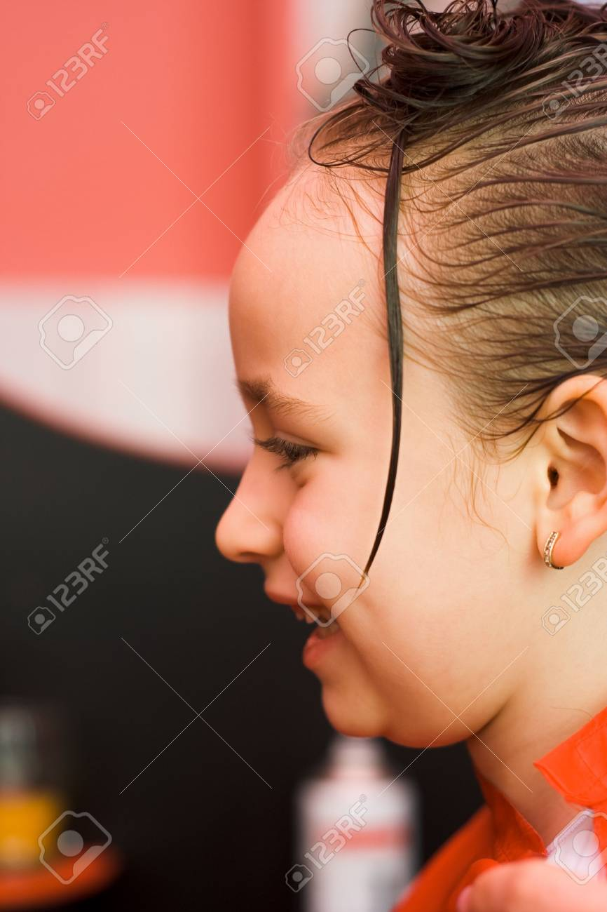 Happy little girl's hair being arranged at the hair stylist Stock Photo - 2457355
