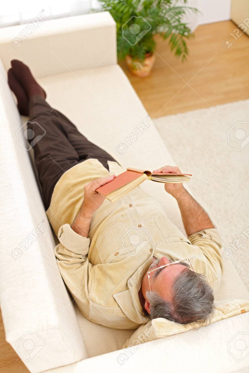 Happy senior man relaxing and reading book on sofa Stock Photo - 8003135