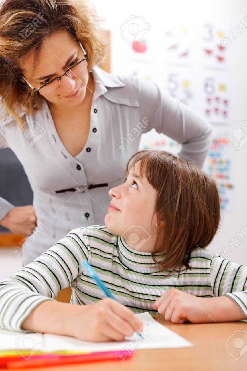 Severe teacher standing behind and looking at schoolgirl Stock Photo - 10030597