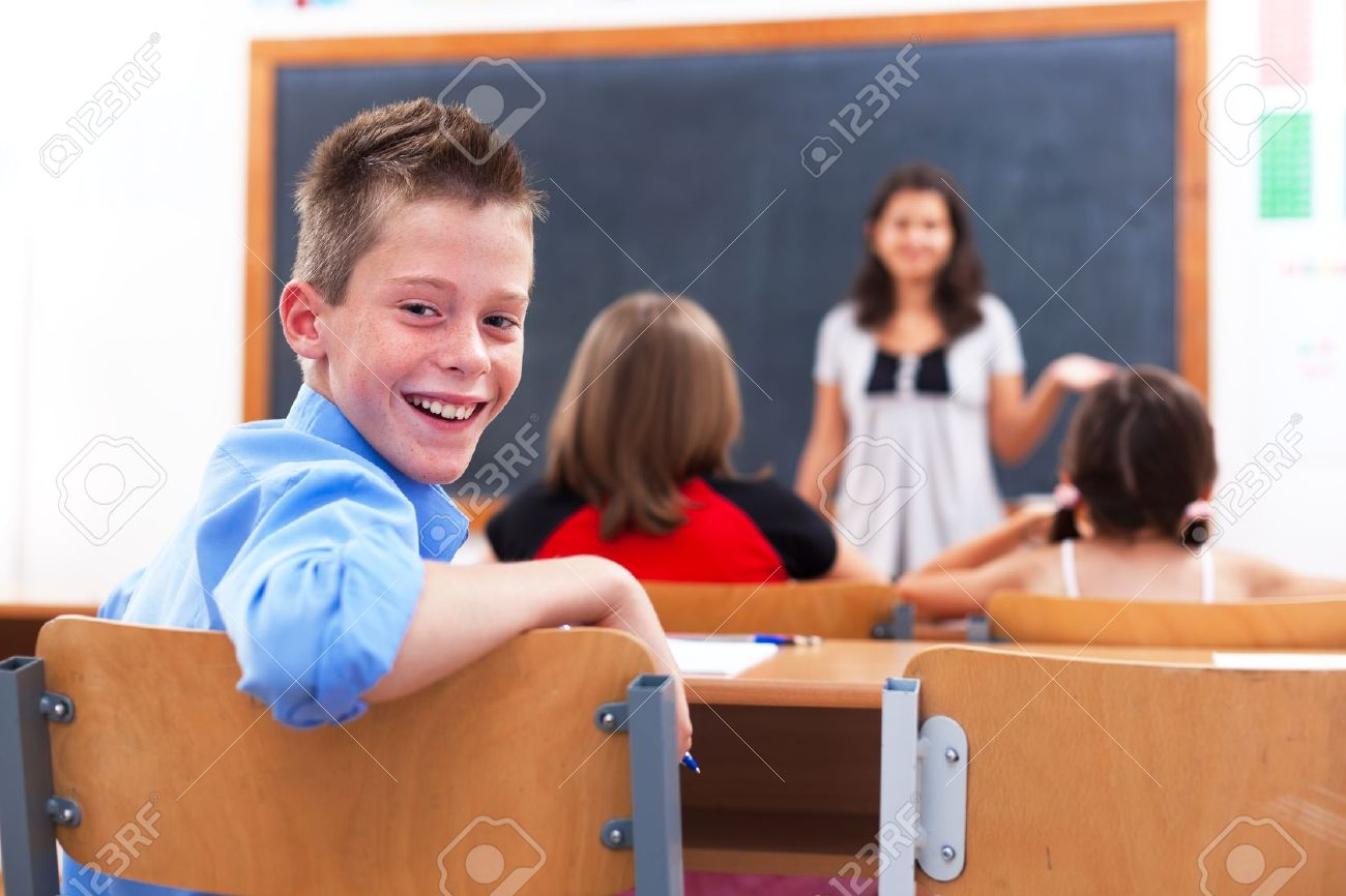 Cheerful School Boy Looking Back In Class Room While The Teacher ...