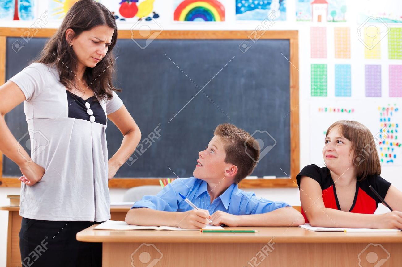 Angry teacher looking at scared, bad boy while his colleague is smiling Stock Photo - 10030580