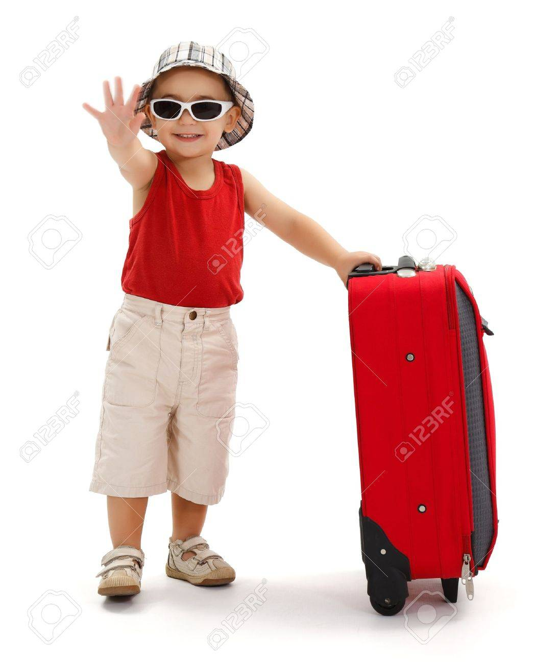 Child standing near luggage, wearing hat and sunglasses, holding his luggage and waving good bye with hand Stock Photo - 10306748