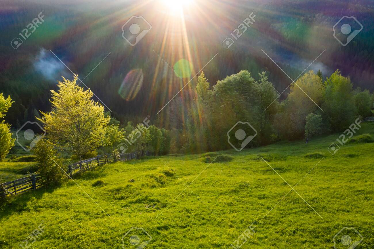 Aerial view of endless lush pastures and farmlands of Transylvania. Beautiful romanian countryside with emerald green fields and meadows. Rural landscape on sunset. - 123692547