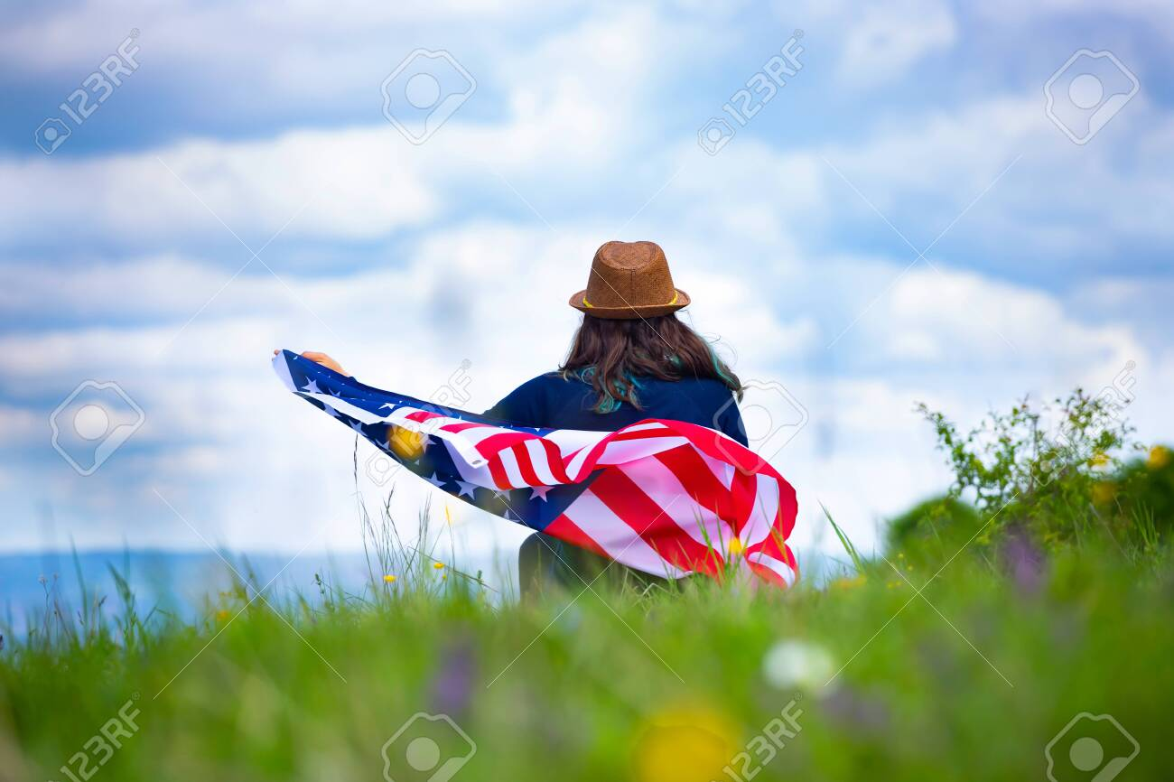 Young woman holding american USA flag. Independence Day or traveling in America concept. - 129689149