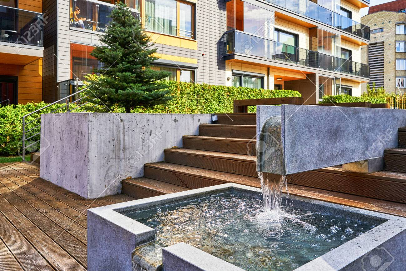 Decorative Water Fountain And Modern Complex Of Apartment Residential  Buildings. With Outdoor Facilities. Stock