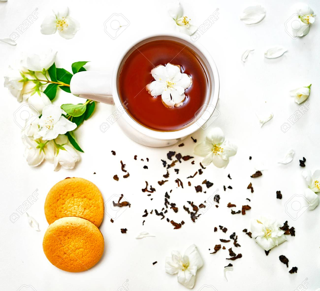 Tea Cup With Dried Leaves And Fragrant Jasmine Flowers And Cookies
