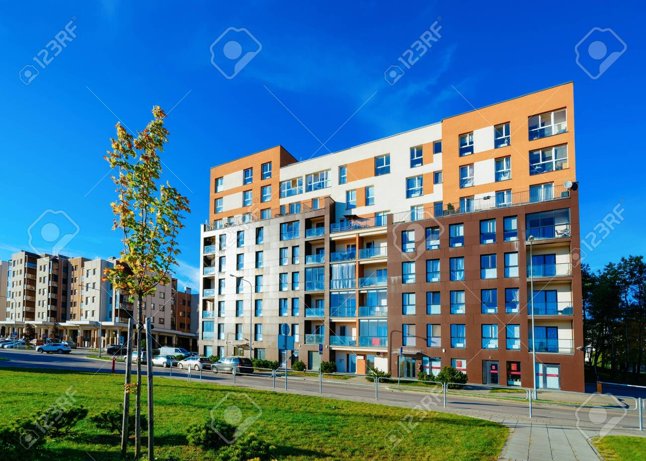Apartment house residential building and cars parked in street - 134404480