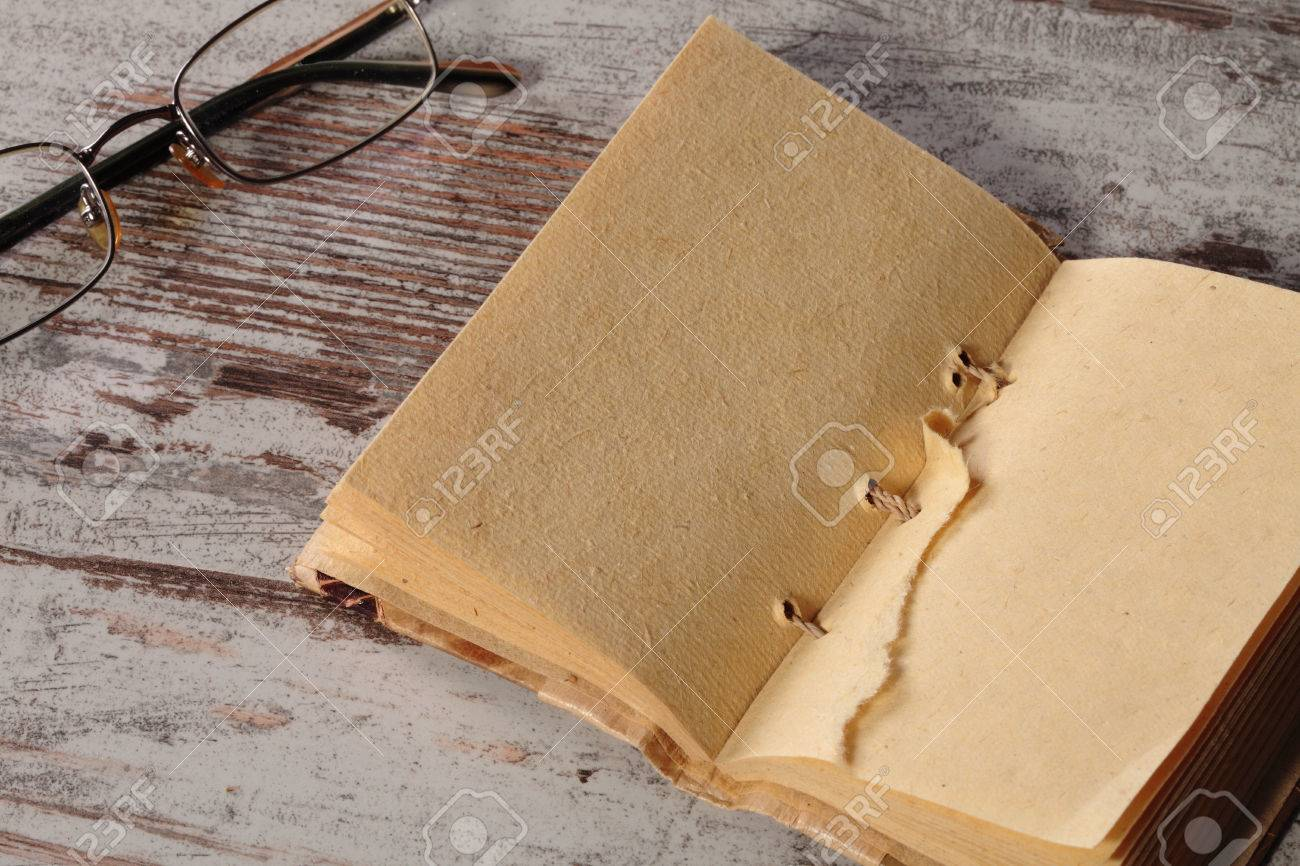 an old notepad and glasses on a wood table Stock Photo - 26239357