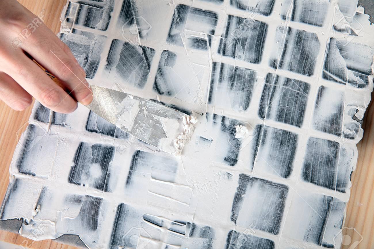 Lavoratore si applica stucco in piastrelle grigie foto royalty