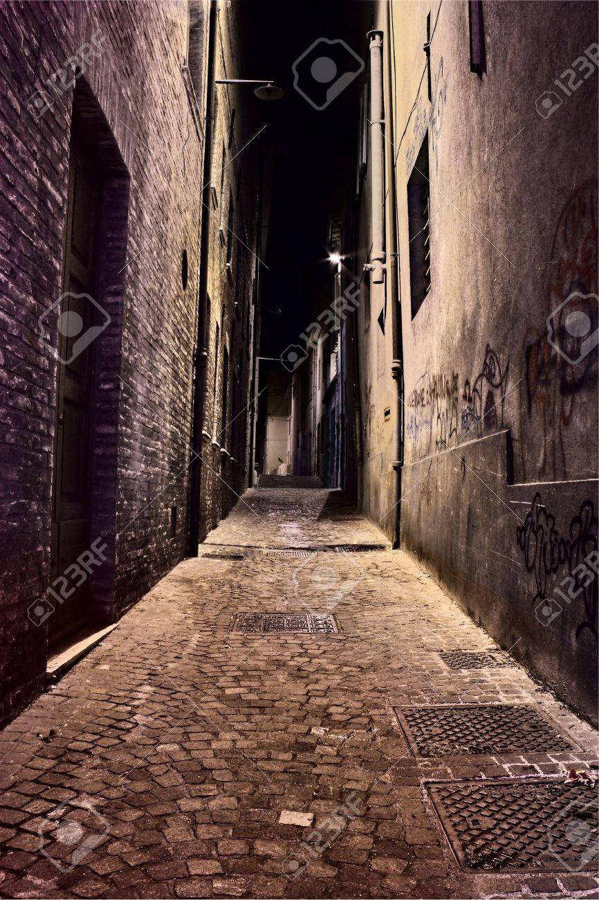 夜 暗い退廃的な通りの古い町のイタリアの汚れた狭い路地 の写真素材