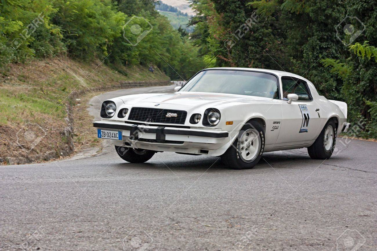 vintage chevrolet camaro z28 in hairpin bend at uphill race rally