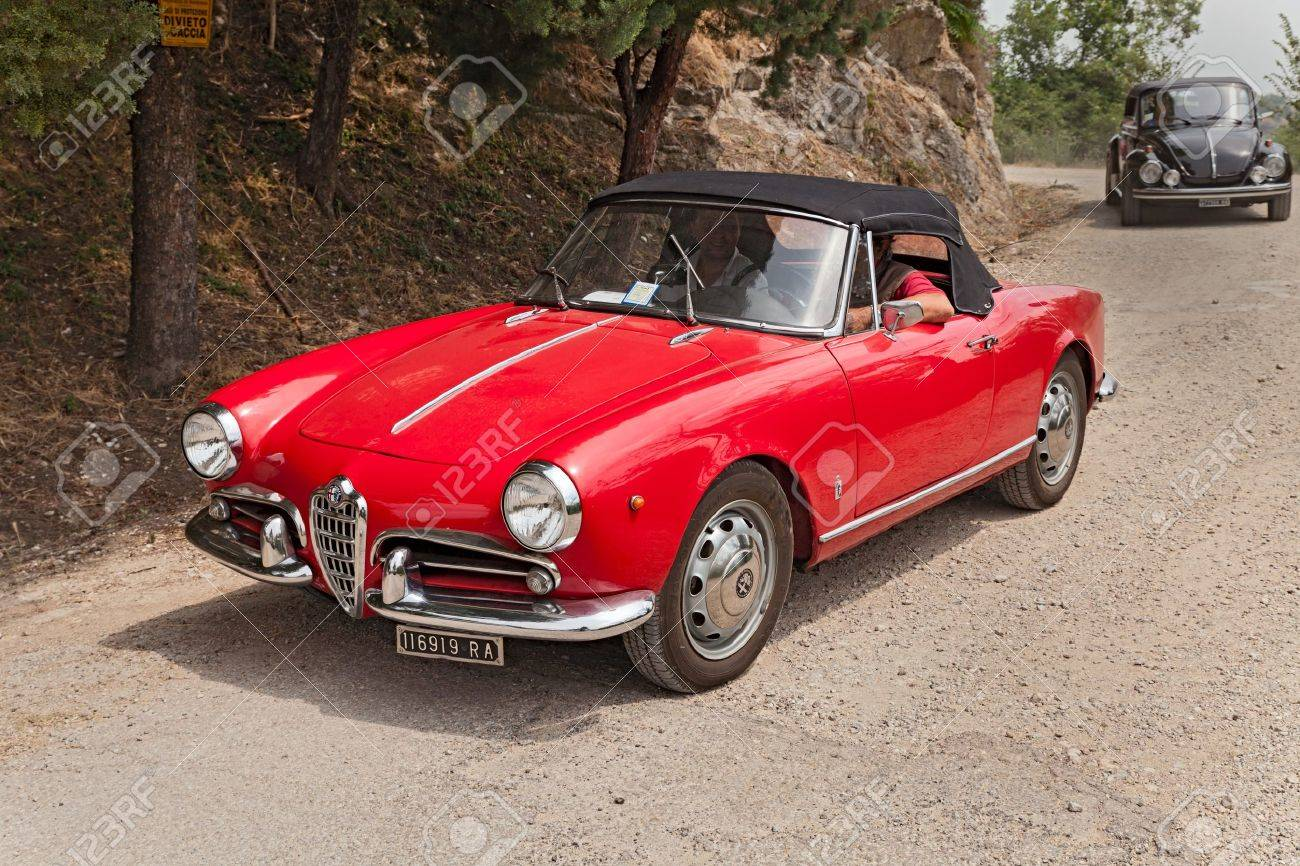 Vintage Car Alfa Romeo Giulietta Spider Runs On A Dirt Road In The Italian  Hills During