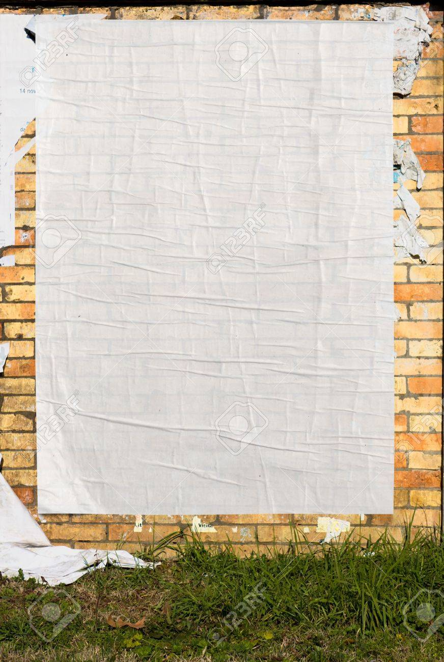 Brick Wall With Blank Poster And Torn Posters Stock Photo