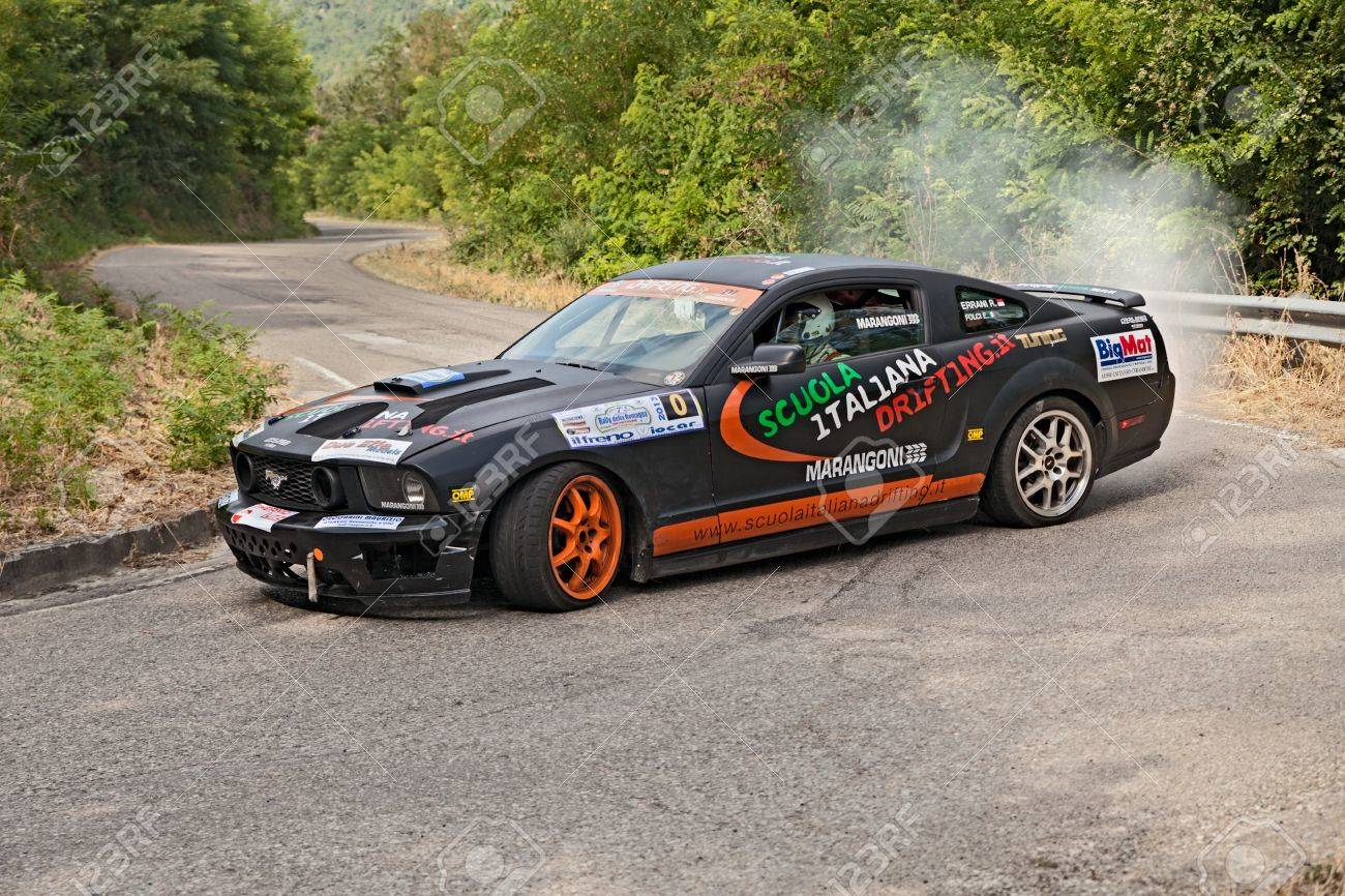 A drift racing car ford mustang in action with smoking tires in hairpin bend at rally