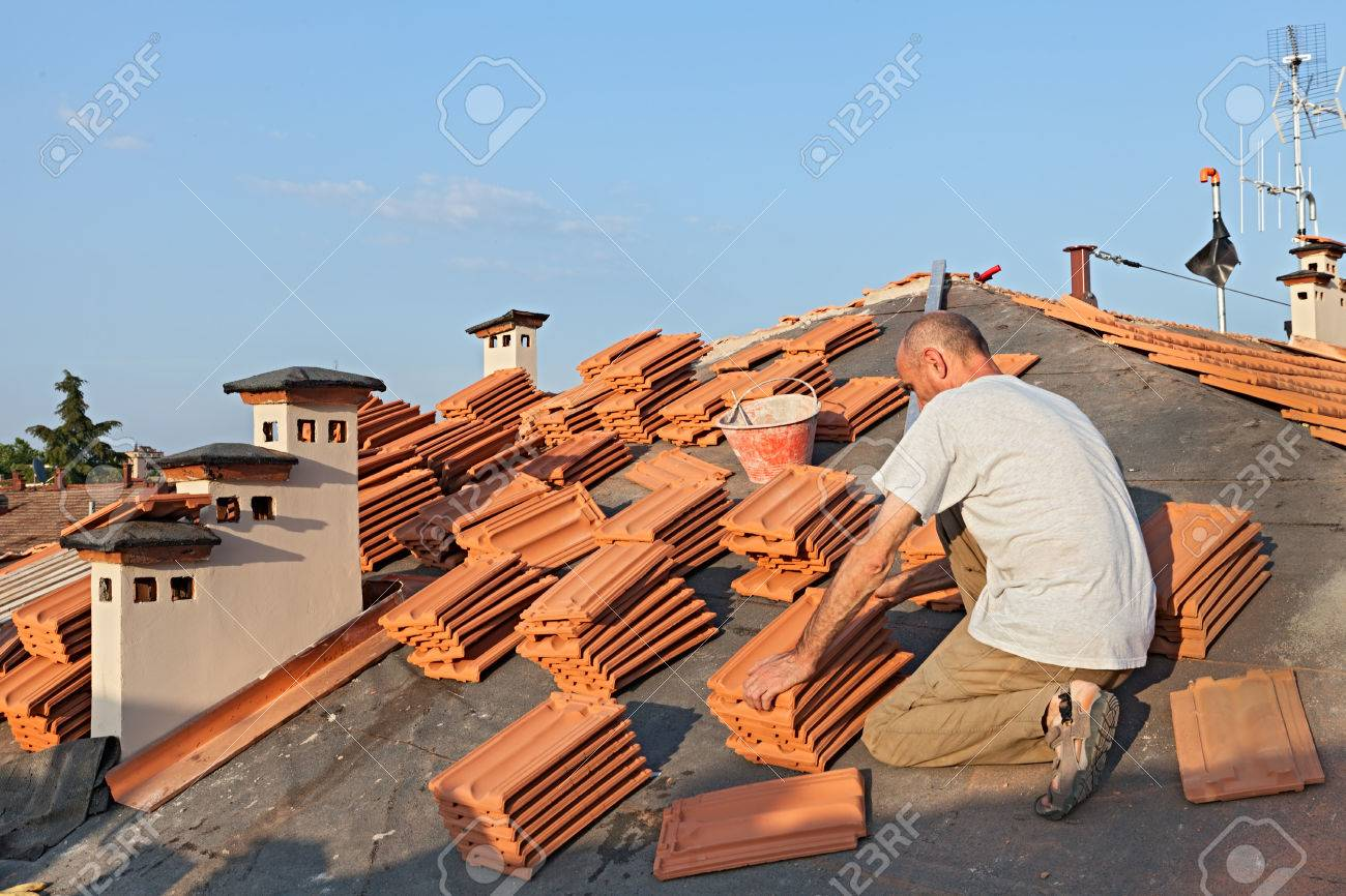 roofing construction worker on a roof covering it with tiles - roof  renovation installation of tar