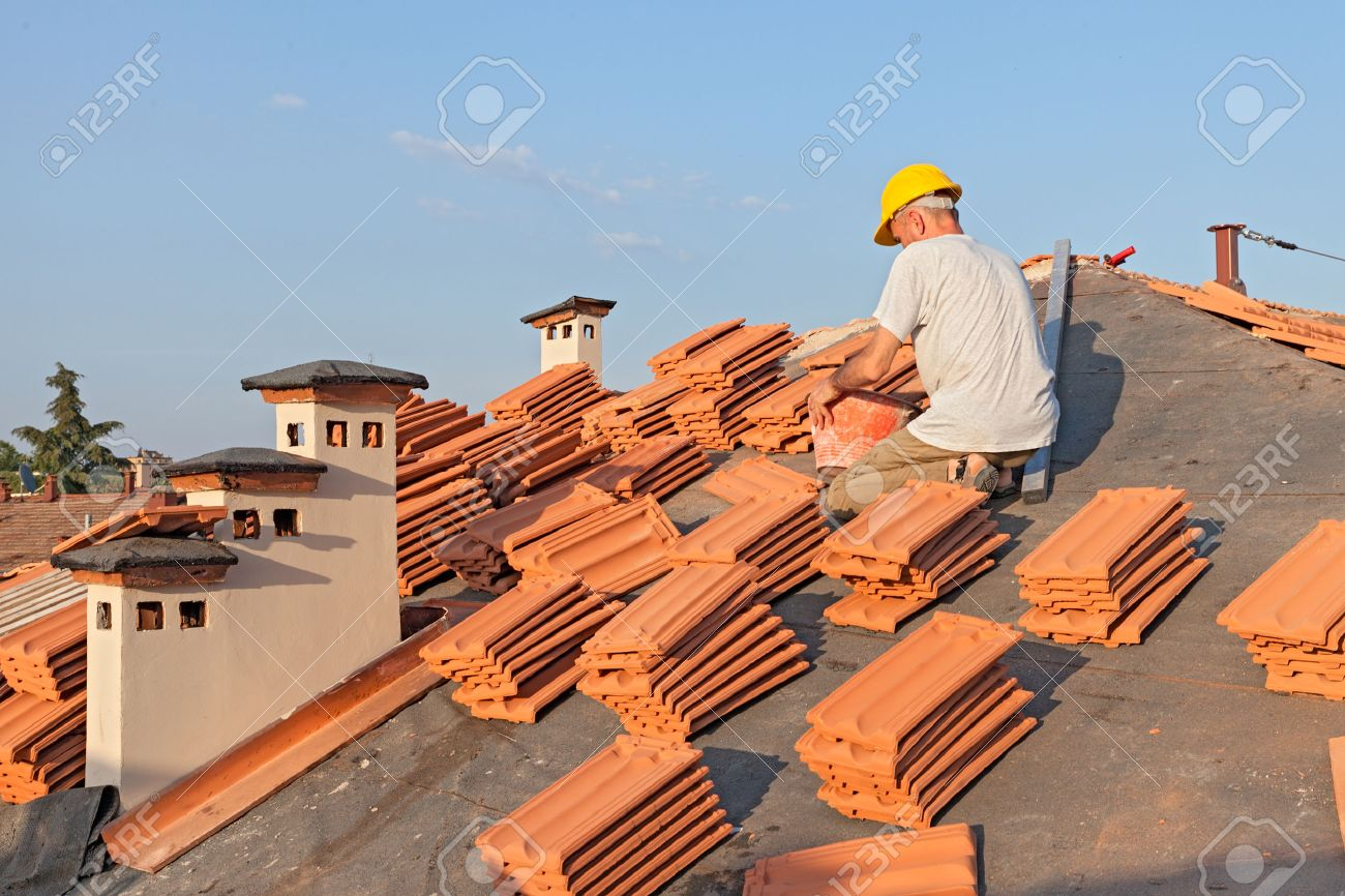 Roofing: Construction Worker On A Roof Covering It With Tiles   Roof  Renovation: Installation