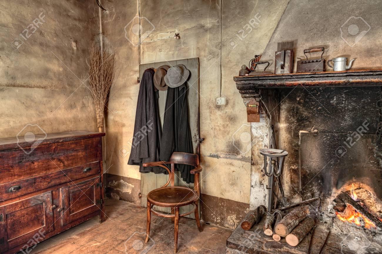 Ferme d\'époque - intérieur d\'une ancienne maison de campagne avec cheminée,  placard de cuisine, anciens manteaux et balai