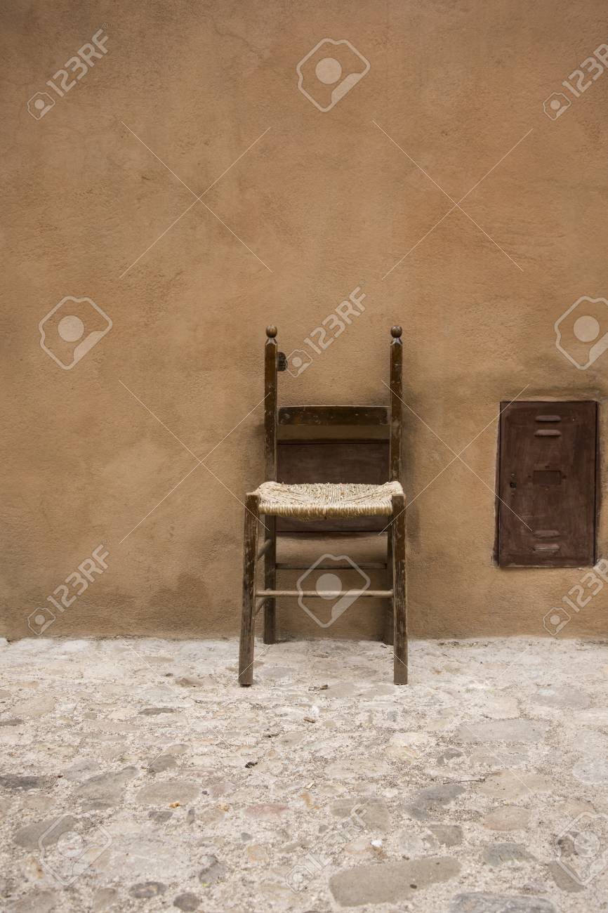 Stock Photo - vintage chair a little broken leaning against a wall outside & Vintage Chair A Little Broken Leaning Against A Wall Outside Stock ...