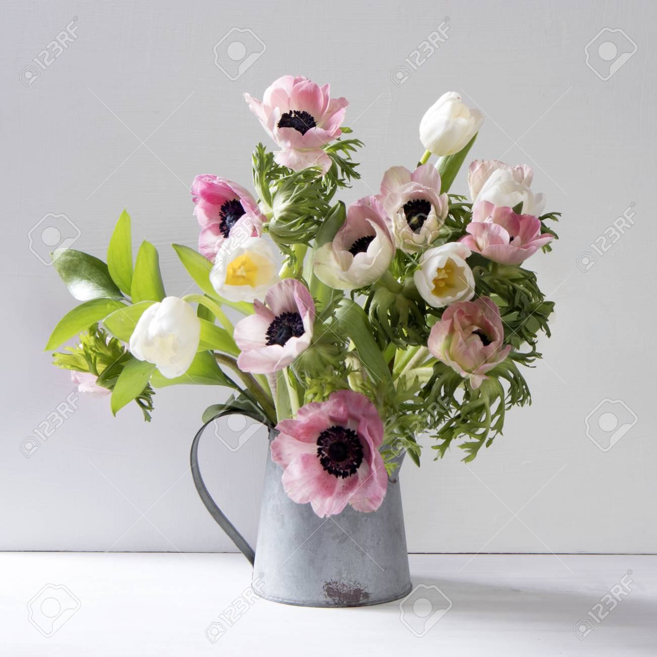 Wedding bouquet of anemones and tulips with ruscus in a jug on stock photo wedding bouquet of anemones and tulips with ruscus in a jug on a black background izmirmasajfo