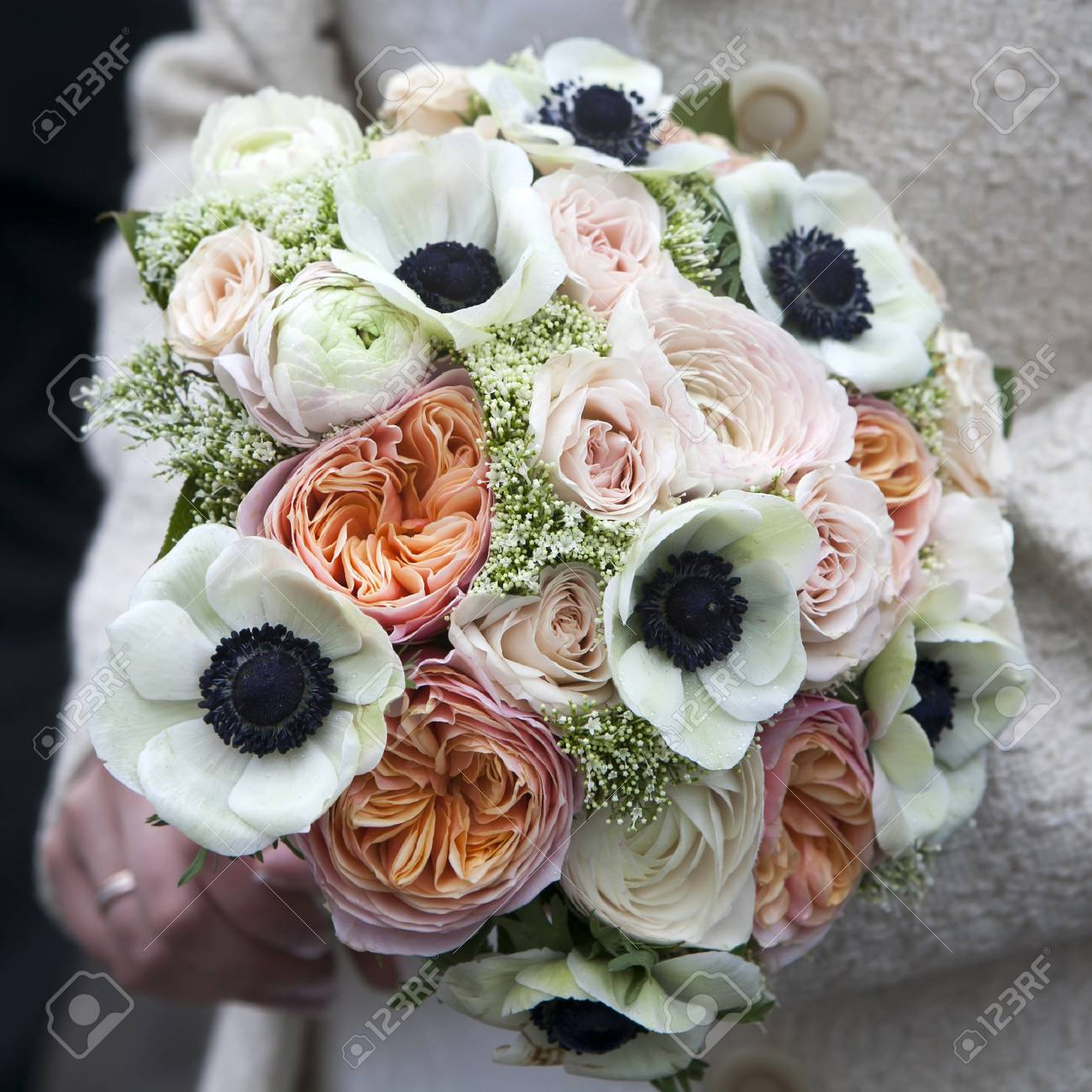 Bride Holds Wedding Bouquet Of Pink Roses And White Anemone And ...