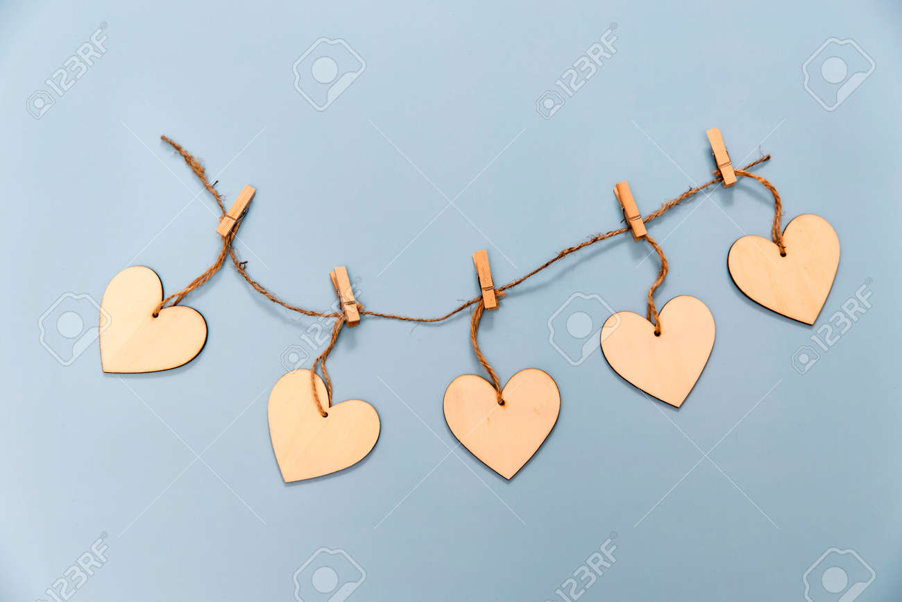 Wooden hearts pinned to a rope with clothespins on a light blue background. Copy space - 162461914