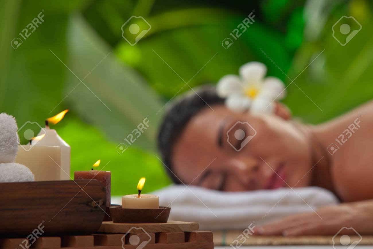 portrait of young beautiful woman in spa environment  blurred face, focused on candles Stock Photo - 13664373