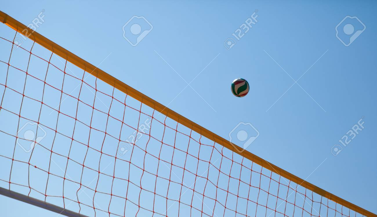 Volleyball ball over net on background of blue summer sunny sky.