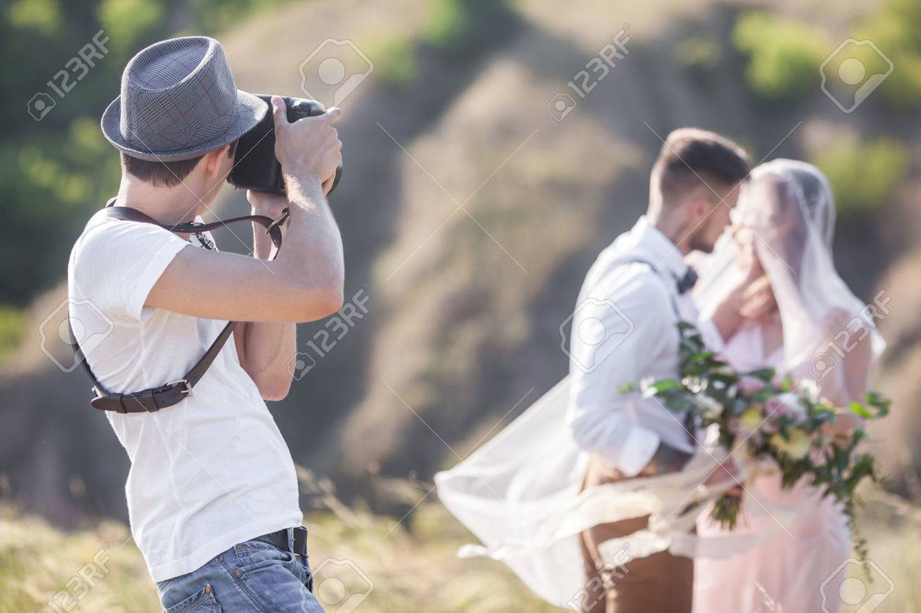 a wedding photographer takes pictures of the bride and groom in nature, the photographer in action - 64145056