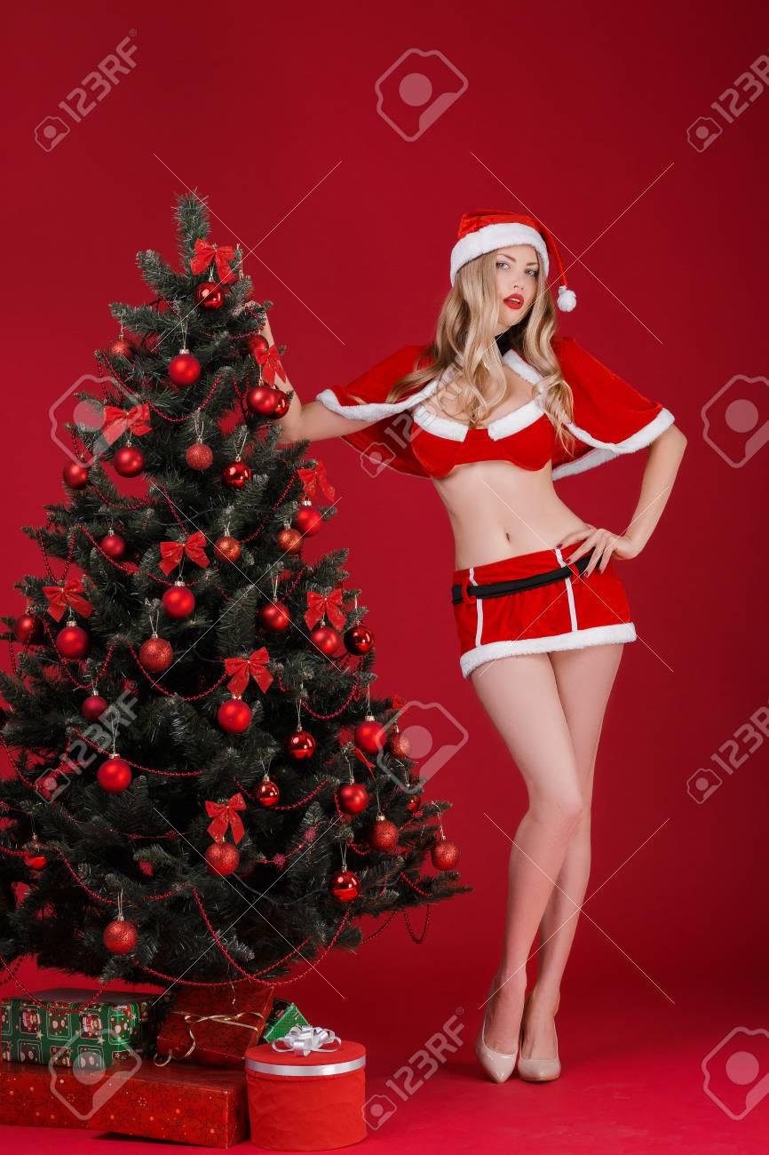 Foto Di Natale Con Donne.Le Donne Sexy Bionda Nei Vestiti Di Babbo Natale Vicino All Albero Di Natale Su Una Priorita Bassa Rossa