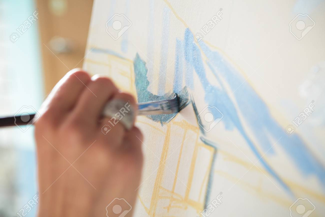 artists hand with brush painting on canvas