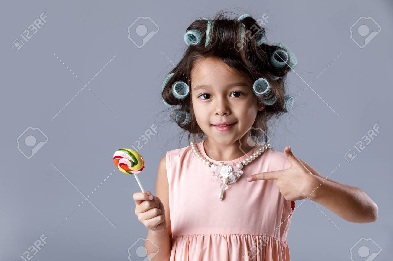 6d20c48b2 Funny little girl in pink dress and hair curlers holding lollipop Stock  Photo - 115760364