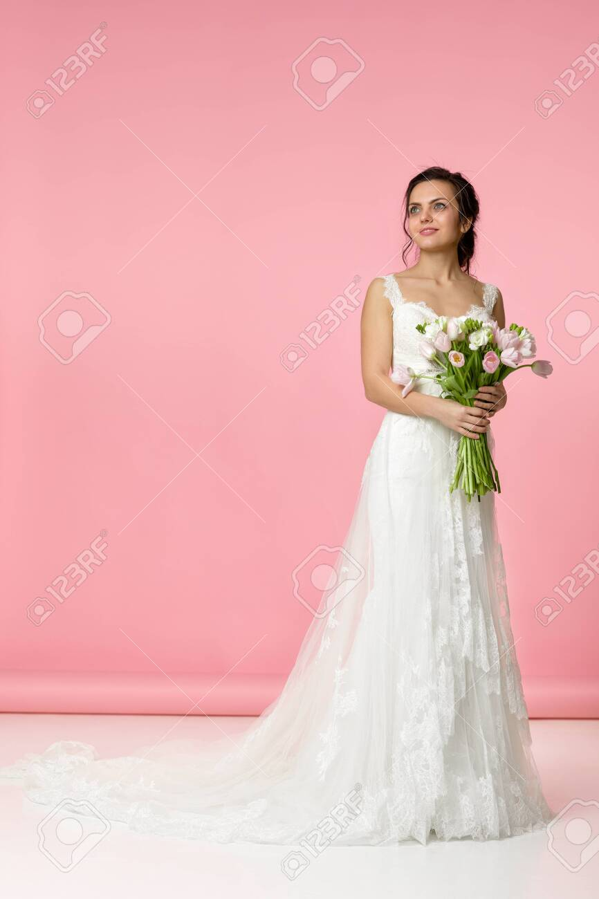 Beautiful Bride With Wedding Bouquet Of Pink Tulips On Pink