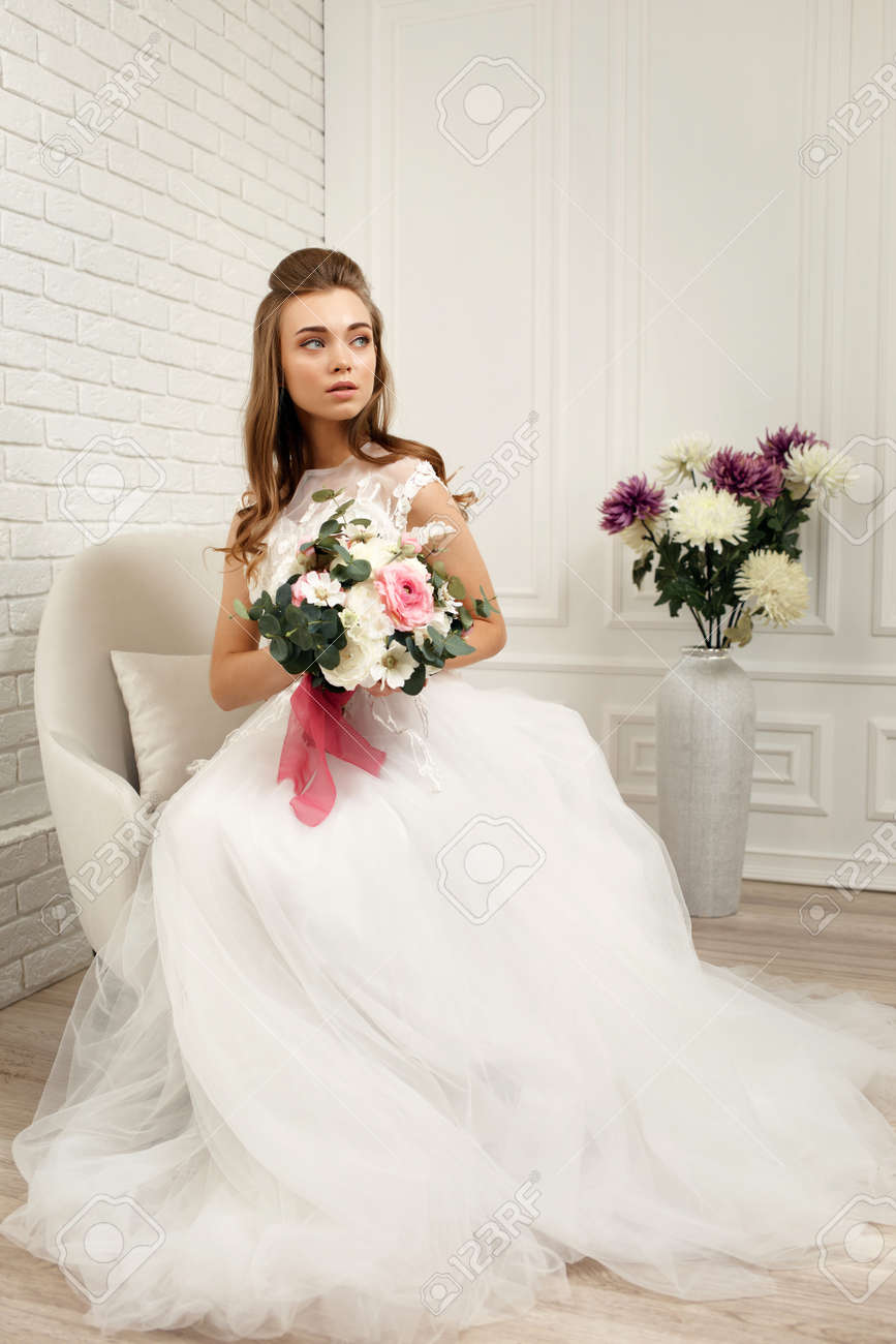 gorgeous beautiful young bride in a luxurious wedding dress with flower bouquet in white studio interior, full lenth - 158463384