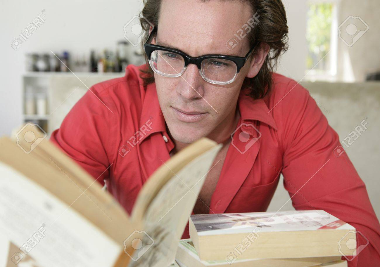 Young man with glasses reading a book - 7597334