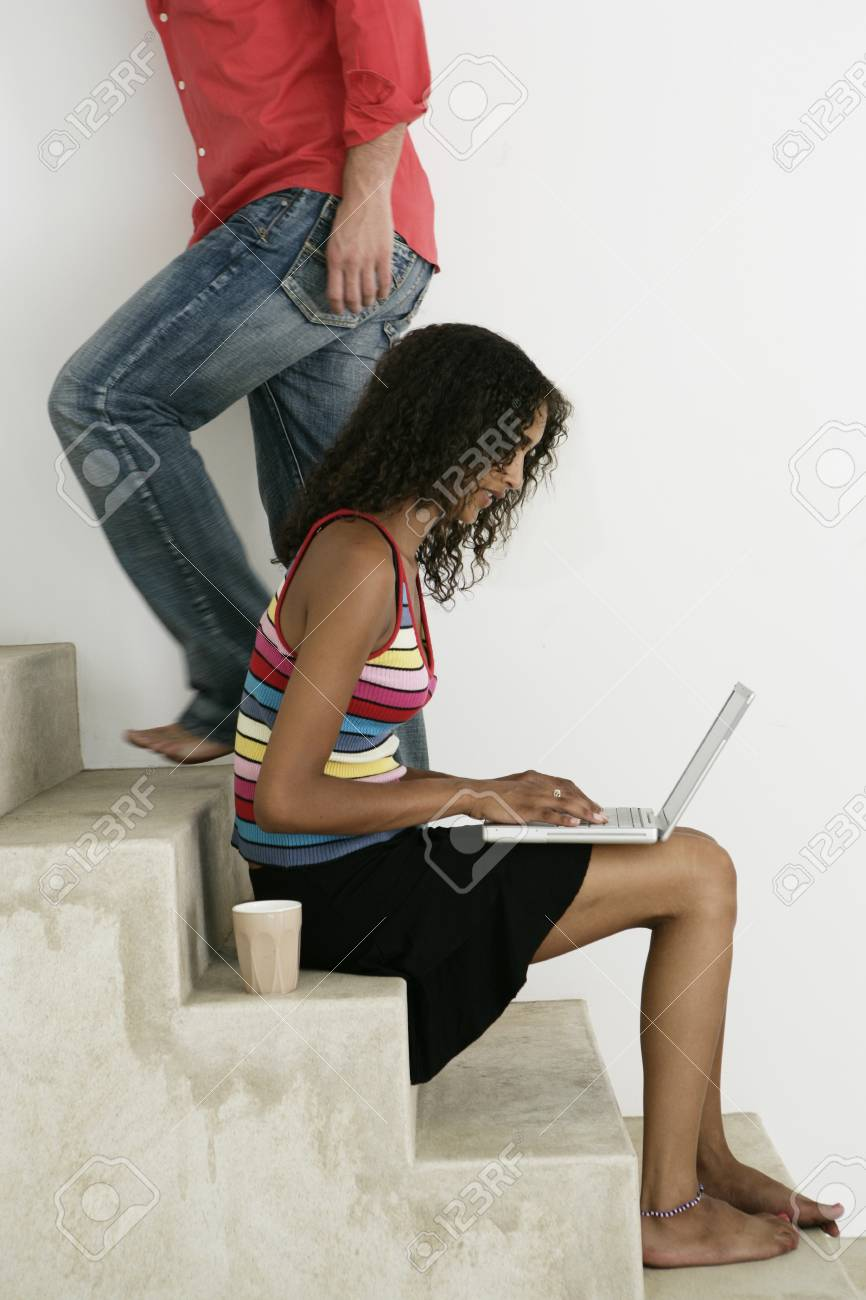 Female working on stairs on laptop and male walking by - 7597348