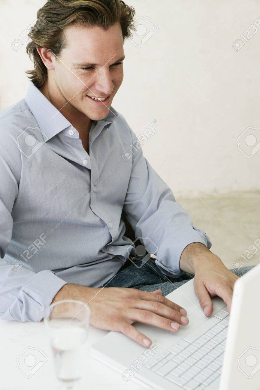 Young male looking content whilst working on laptop at home - 7597379