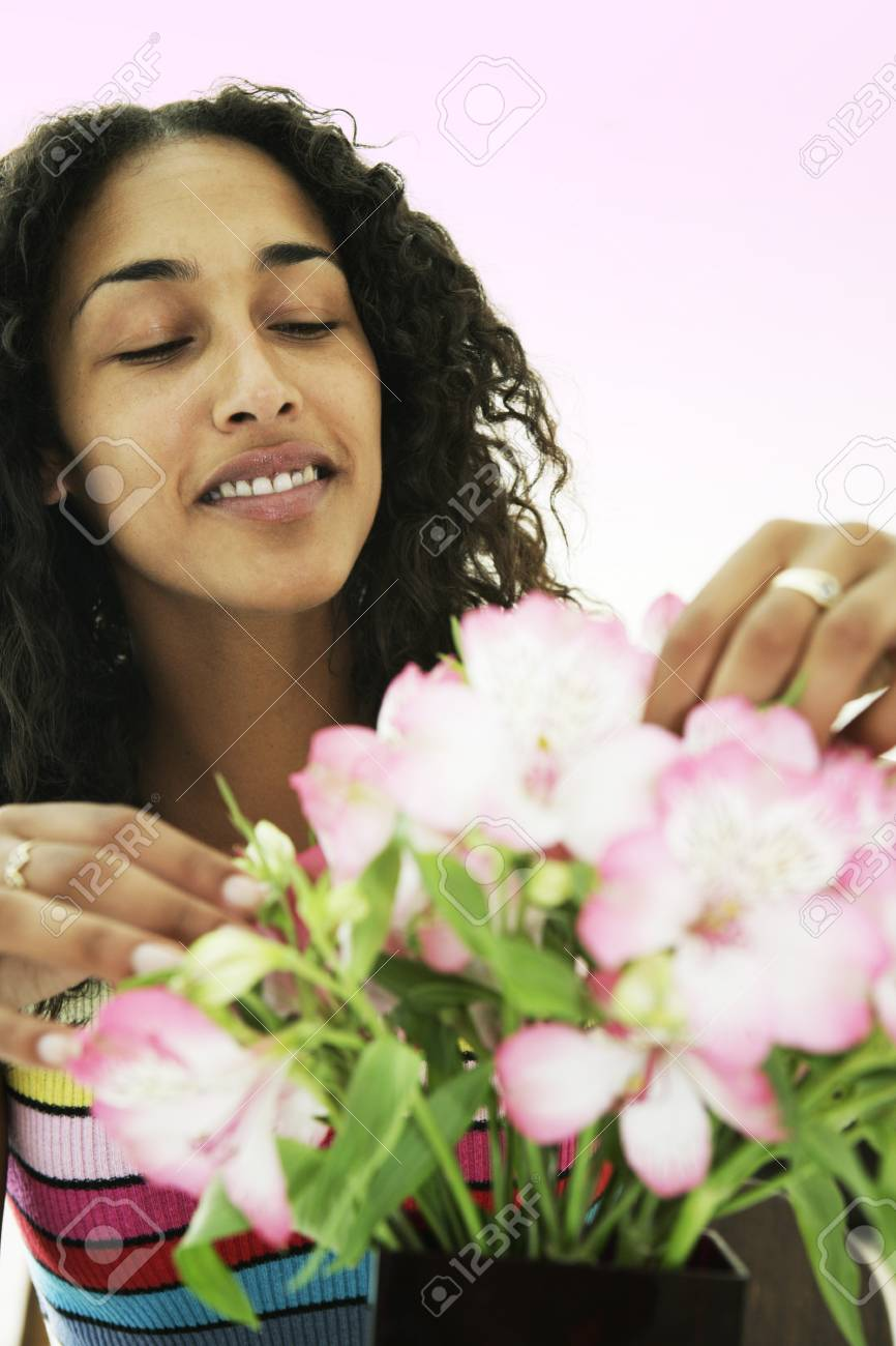 Female arranging and smelling flowers - 7597264