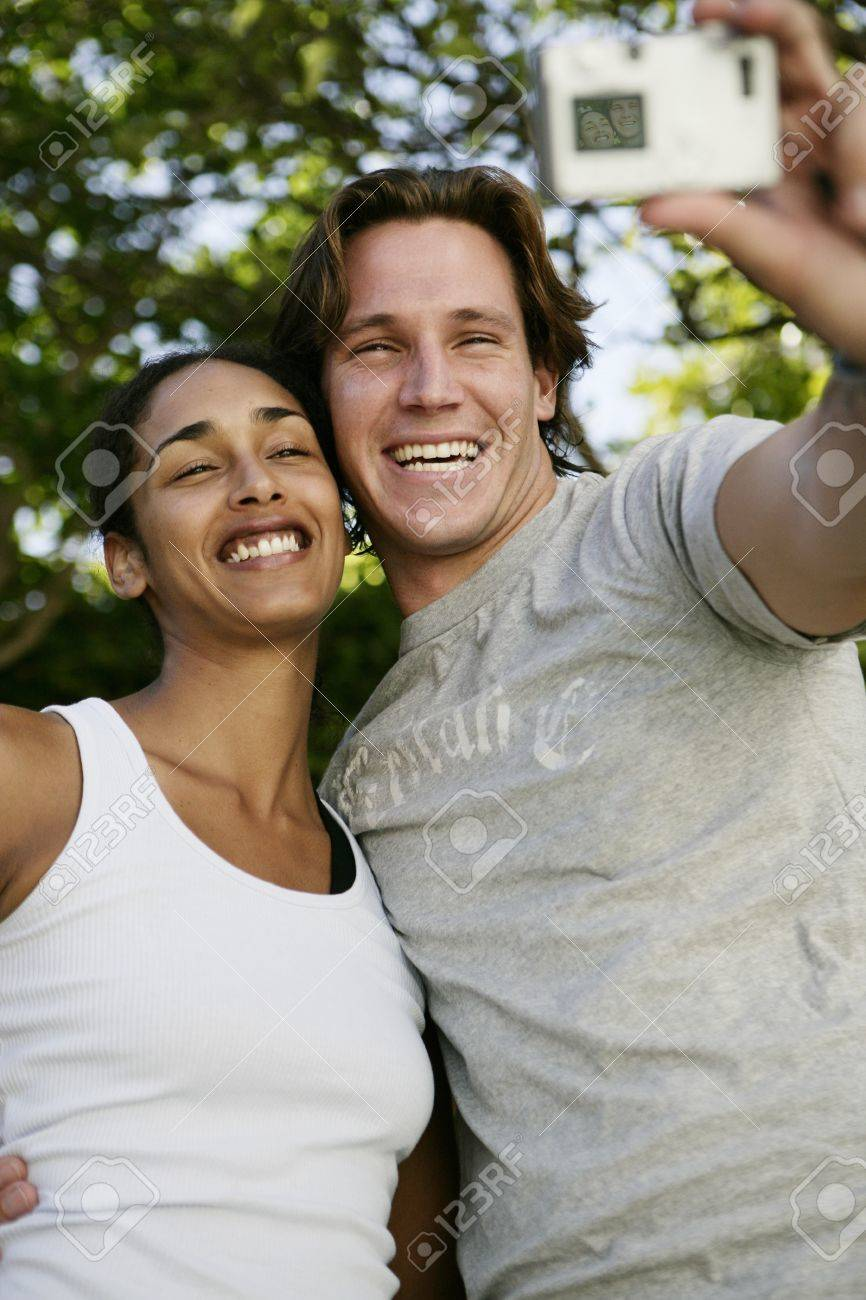 Couple taking self portrait with digital camera - 7597478