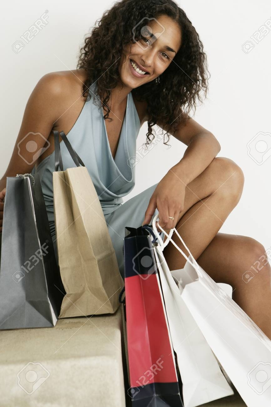 Female looking cheerful to camera with shopping bags - 7597433