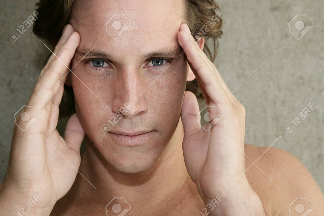Young man with headache and holding his temples - 7597359