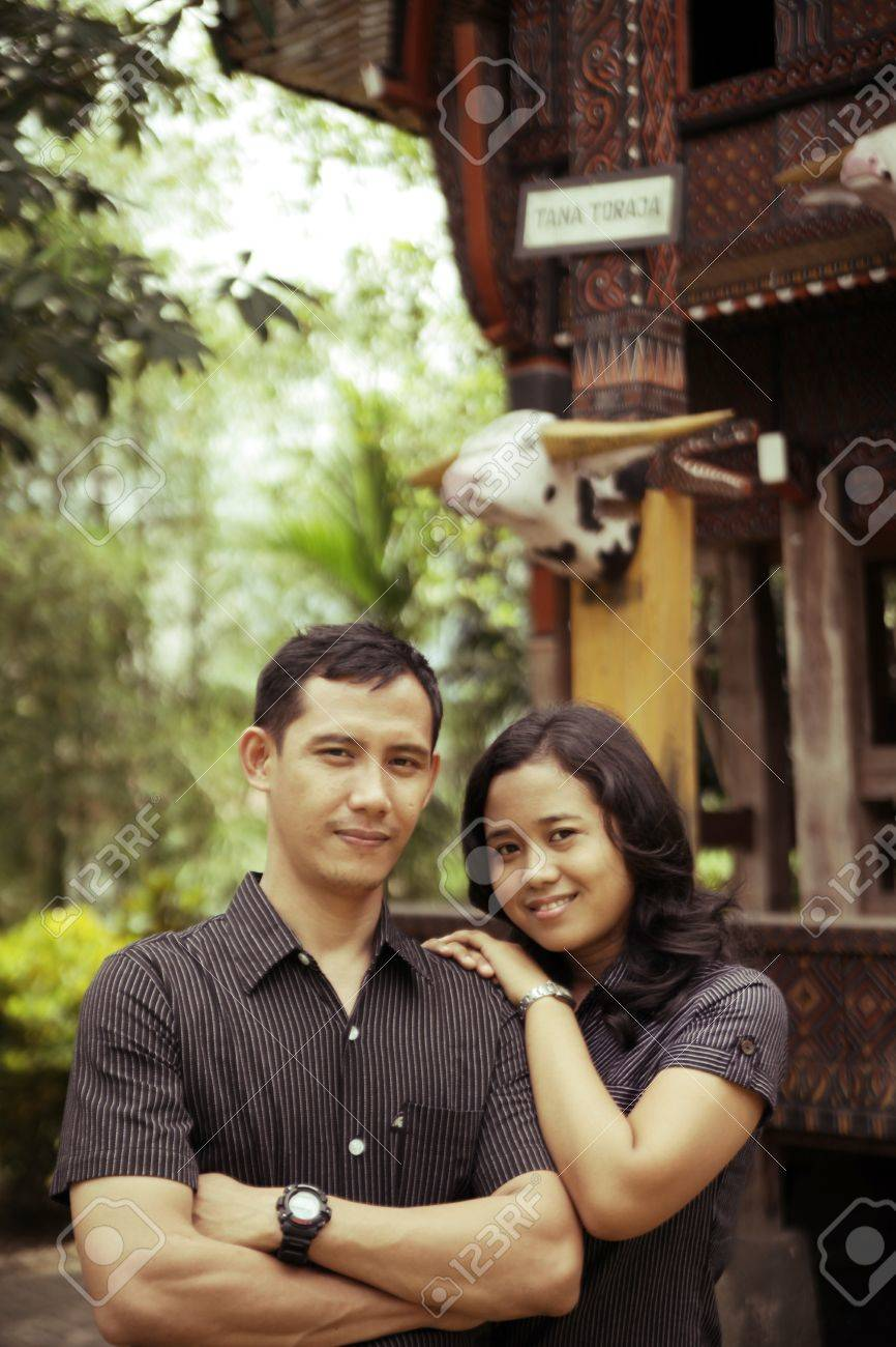 Southeast asian couple outdoor at front of traditional tana toraja house Stock Photo - 11370107