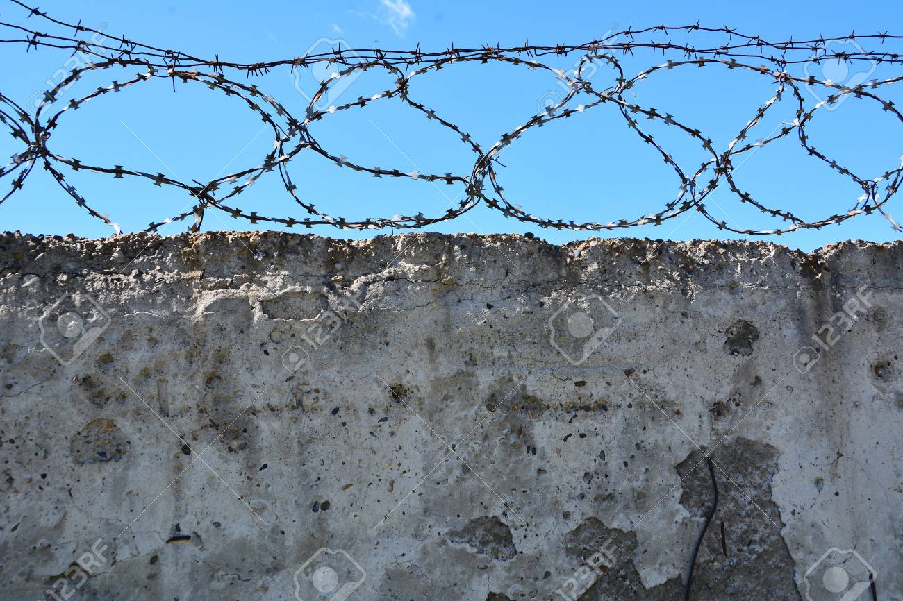 Concrete Wall, Against The Backdrop Of Barbed Wire, The Concep Stock ...
