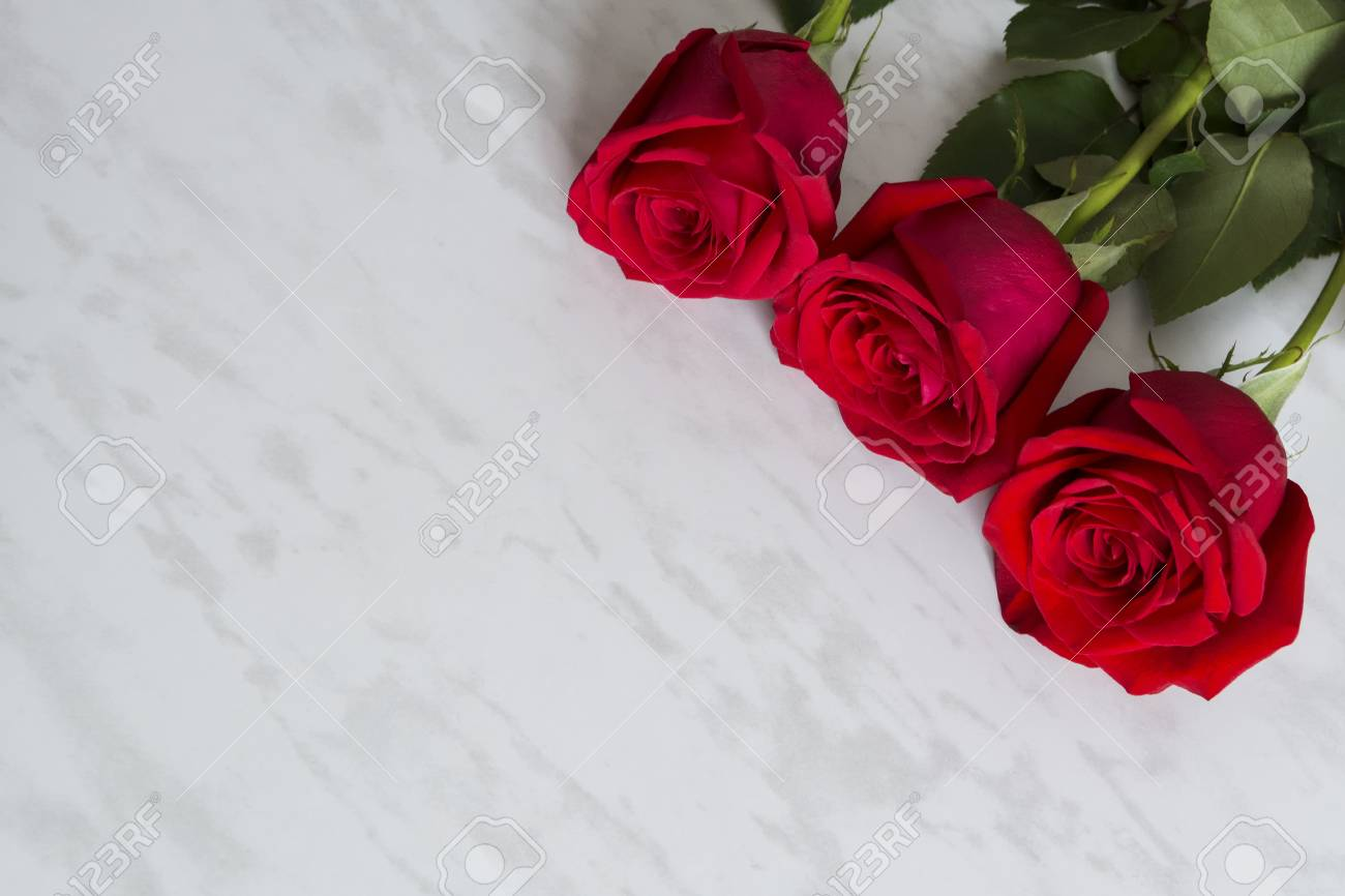Three Roses Laying In Diagonal Group On The Marble Background